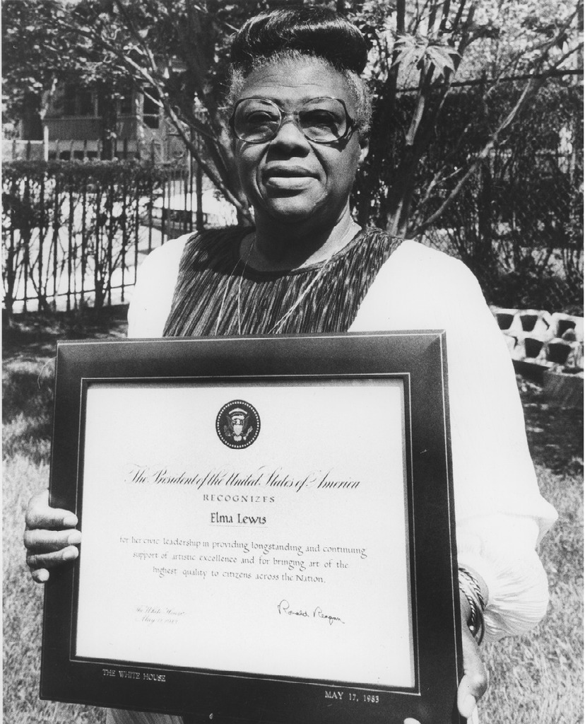 Elma Lewis standing with award from President Ronald Reagan