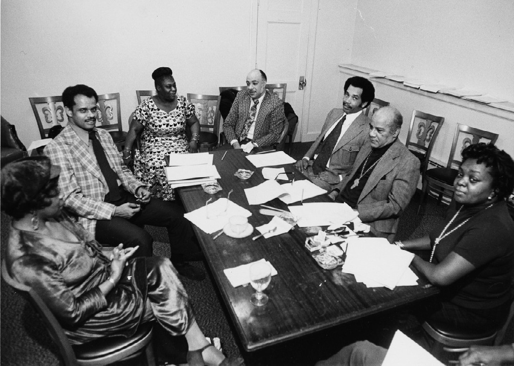 Elma Lewis sitting in a meeting room with a group of adults